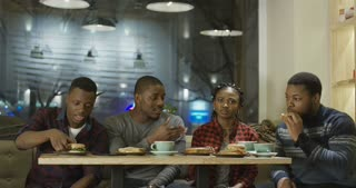 Group of laughing African-American friends having fun eating sandwiches and burgers drink coffee and then making selfie for social media in cozy cafeteria.