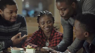 Group of laughing African-American men and girl watching something on smartphone and laughing while chilling in cafe.