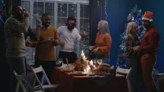 Group of laughing friends and family gathering at home for Christmas and having fun while dancing and celebrating