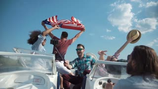 Group of laughing friends having fun on boat and taking selfie