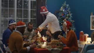 Group of laughing happy friends enjoying Christmas party at home and carving roasted turkey having fun on dinner