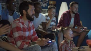 Group of multiethnic men and teens gathering on sofa at home and playing videogame with gamepads