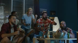Group of multiracial men and woman on sofa watching sport game they are unhappy with the result of the game