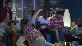 Group of multiracial men on sofa at home making money bets for sport game while watching championship together