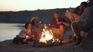 Group of multiracial people sitting around campfire grilling marshmallows and having fun on coast