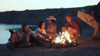 Group of multiracial people sitting around campfire grilling sausages and having fun on coast