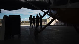Group of people standing in hangar and looking at plane