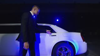 Group of rock musicians walking out of limo and giving autographs to fans while photographers taking shots on red carpet