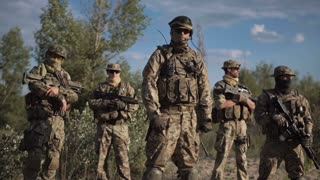 Group of soldiers in a camouflage and the hidden persons with weapon pose and look in the camera
