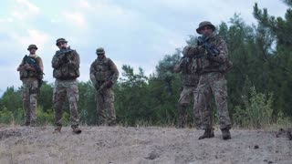 Group of soldiers in a camouflage and with weapon carry out investigation of the territory