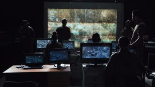 Group of soldiers or spies in dark room with large monitors and advanced satellite communication technology launching a missle. Includes flashing yellow light