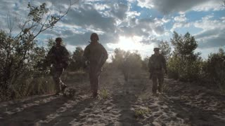 Group of soldiers walking together with equipment on a battlefield