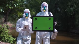 Group of two biochemists in protective suits posing and looking at camera on background of nature and holding in hands frame with chromakey with red dirty river on background