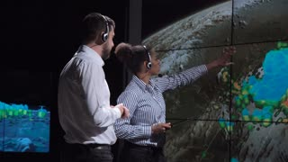 Group of two scientists observing and tracking hurricane on map and analyzing weather. Elements of this image furnished by NASA