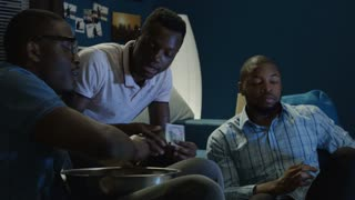 Group of young African-American men betting money while watching sport games at home on sofa