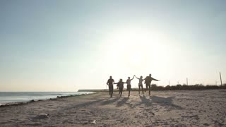 Group of young content people holding hands and running together along seaside in sunset