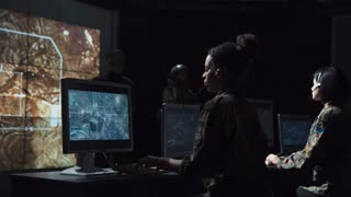 Group of young male and female soldiers in headphones and on computers in communications center coordinating and launching a missile