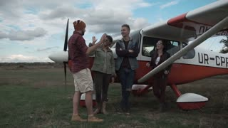 Group of young people talking next to small airplane outdoors