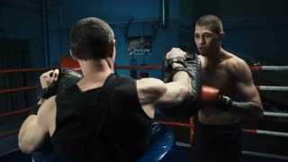 Handheld shot of shirtless muscular boxer with tattooed body working out on ring in gym attacking coach with punching bags.