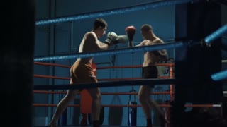 Handheld shot of two shirtless men in boxing gloves fighting and training Thai box moving on square ring.