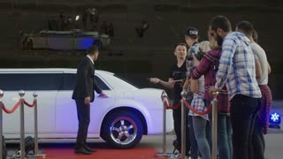 Handsome adult man in tuxedo walking on red carpet and giving autographs to fan people