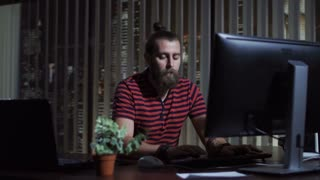 Handsome bearded man sitting at computer in office and working in the evening