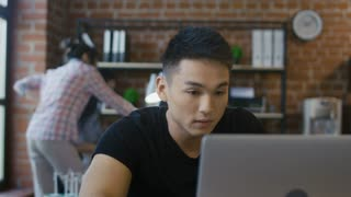 Handsome Korean man working at computer in office and giving wonderful smile at camera