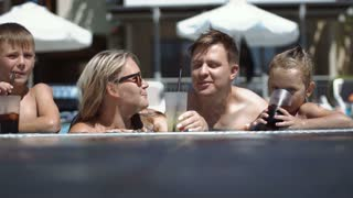 Happy family drinks coctails and talking in pool in hotel
