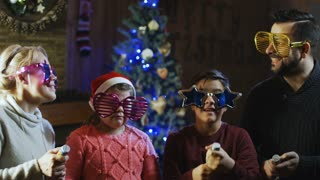 Happy young family celebrating Christmas in colourful fun shaped glasses in front of a decorated Christmas tree counting down to let of small handheld fireworks as they laugh and joke