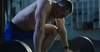 Heavily breathing shirtless athletic man with barbell on floor of gym recovering power looking extremely tired.