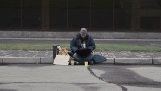 Homeless man sitting at laptop winning a lot of money and starting to celebrate and dance