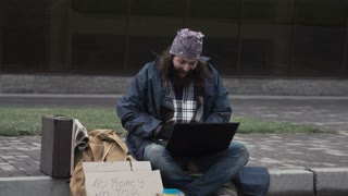 Homeless man sitting at laptop winning a lot of money and starting to celebrate
