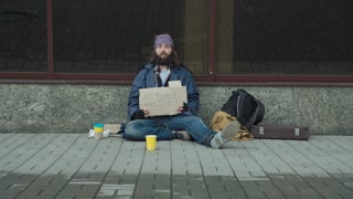 Homeless man with no money, no job cardboard sign sitting on pavement