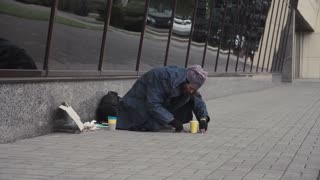 Homeless person taking coins from pavement on city street