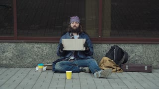 Homeless poor man sitting on pavement with empty cardboard and looking at camera
