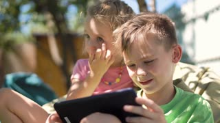 Little boy and girl sitting in backyard and using tablet spending time together