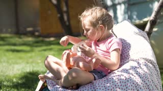 Little girl relaxing in armchair in garden playing and feeding baby doll