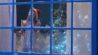 Little girl wearing Santa hat and leaning with face to glass of window expecting Christmas holiday and looking away