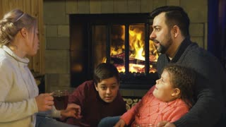 Loving parents with children sitting near fireplace and Christmas tree having fun and drinking tea