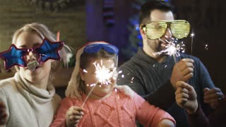 Loving parents with kids wearing festive glasses and holding burning sparkles having fun on New Year