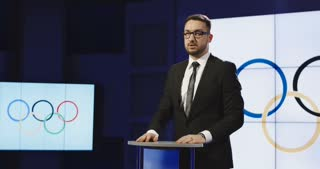 Male middle-aged news anchor wearing glasses standing behind a podium with the Olympic Flag reading the Olympic sports news
