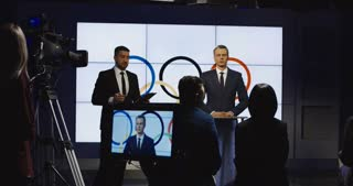 Male official representative talking to journalists from stage standing against screen with symbol of Olympic Games giving speech
