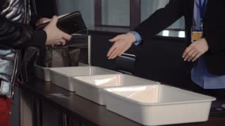 Male passenger placing belongings in a plastic tray at the x-ray scanner which will be passed through and checked separately in a close up view of his hands.