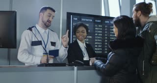 Male passenger placing his thumb on a fingerprint scanner at the check-in counter as a security official checks his passport. 4K shot on Red cinema camera.