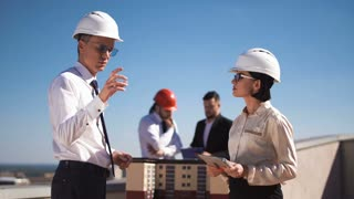 Man and woman architects standing in hardhats with tablet and collaborating at house model shaking hands and looking at camera
