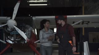 Man discussing over digital tablet in aircraft hangar with woman