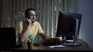 Man in casual wear working in office at night sitting at laptop and communicating with phone