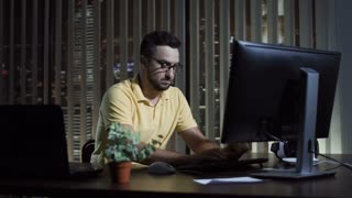 Man in glasses sitting at computer in office and working at night