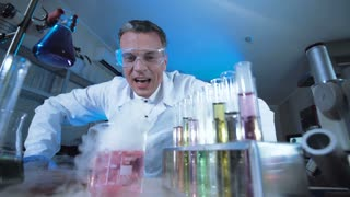 Man in medical gown and glasses watching chemical reaction in test tube