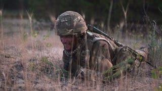 Man in military uniform with gun crawling alone on ground in field